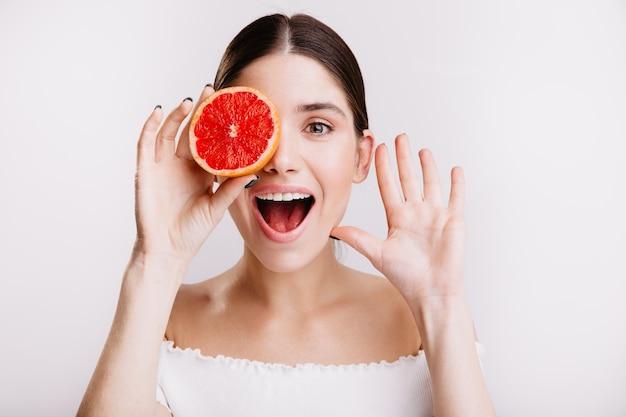Donkerharige dame met een gezonde huid met een glimlach, die haar ogen bedekt met rode grapefruit.