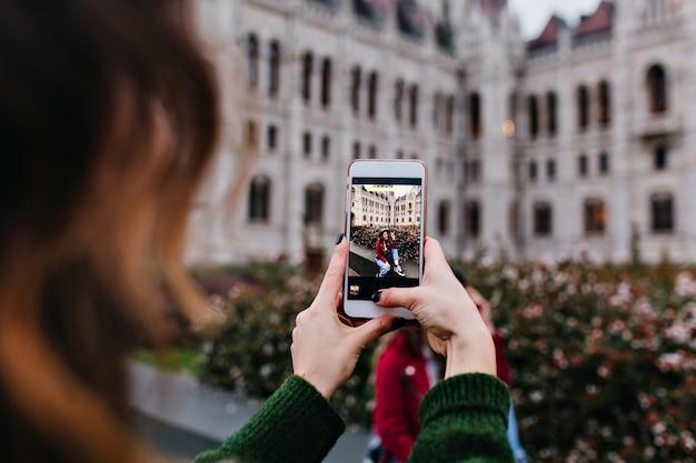 Donkerharige dame met telefoon voor foto van haar vriend