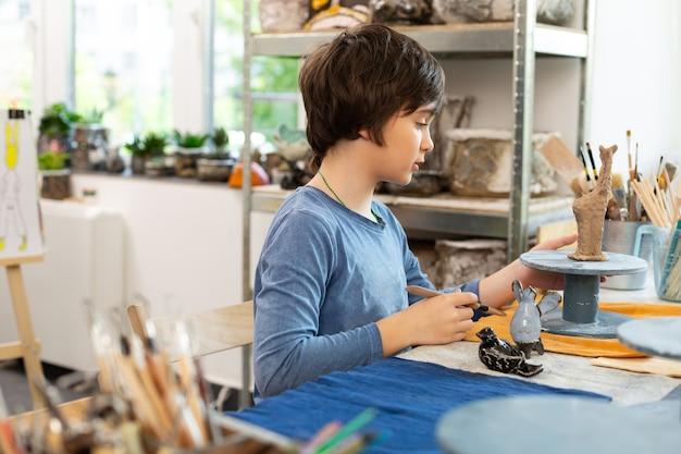 Donkerharige getalenteerde jongen die figuren beeldhouwen met klei