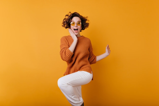 Donkerharige jonge vrouw springen en geluk uitdrukken. portret van verrast positief meisje met kort kapsel en arm tatoeage dansen met een glimlach.
