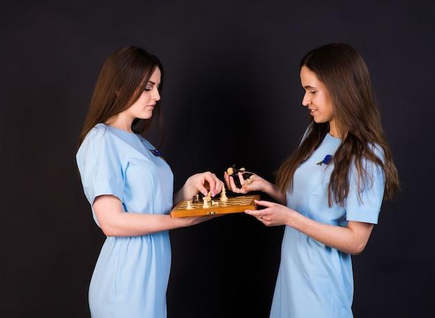 Donkerharige jonge vrouwen in een blauwe jurk schaken op gele en zwarte muur