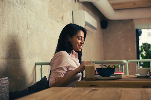 Donkerharige jongedame zit aan de houten tafel in een café en glimlacht terwijl ze geniet van haar salade
