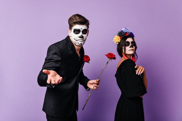 Donkerharige jongeman die zich niet bekommerde om wat zijn vriendin beledigd was. portret van een verbaasde man met roos in zijn handen en arrogante vrouw met gezichtsart.