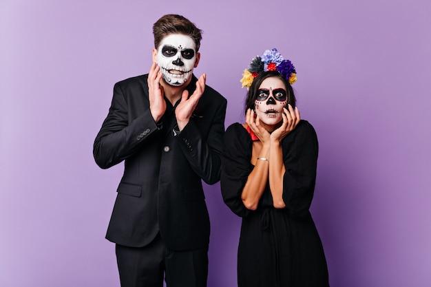 Donkerharige jongen en meisje in zwarte outfit met halloween-make-up bang en verbaasd gebaren