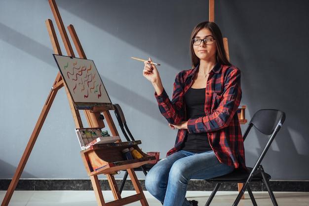 Donkerharige kunstenaar met een penseel in zijn hand en tekent een afbeelding op canvas.