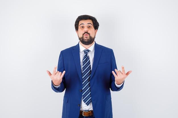 Donkerharige man doet rock-in-roll-gebaar in wit overhemd, donkerblauwe jas, stropdas vooraanzicht.