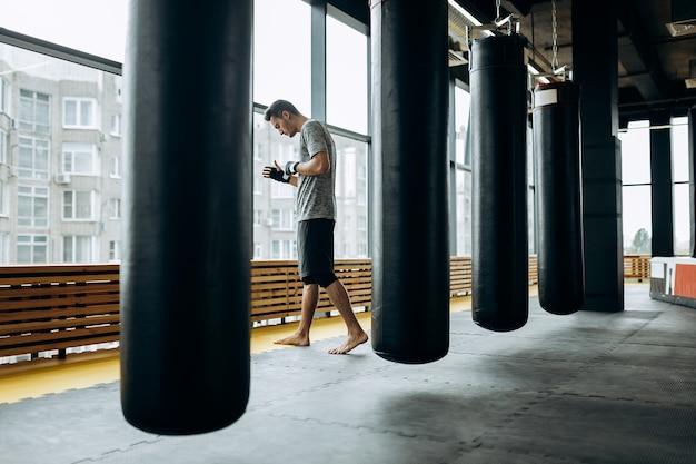Donkerharige man gekleed in het grijze t-shirt en zwarte korte broek staat achter de hangende bokszak naast panoramische ramen in de boksschool.
