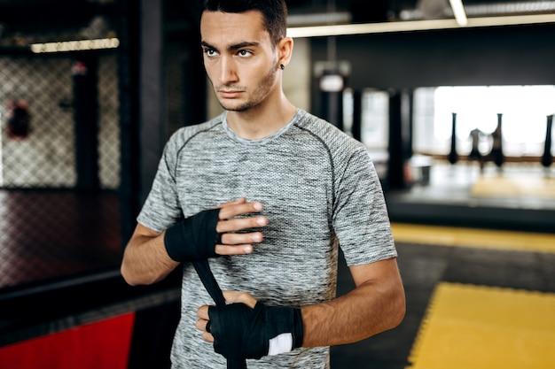 Donkerharige man gekleed in het grijze t-shirt en zwarte korte broek staat in de sportschool naast de boksring en wikkelt een handverband om zijn hand.