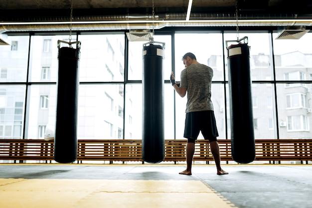Donkerharige man gekleed in het grijze t-shirt en zwarte korte broek staat naast bokszakken tegen de achtergrond van panoramische ramen in de boksschool.