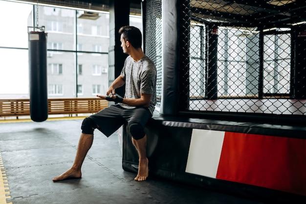 Donkerharige man gekleed in het grijze t-shirt en zwarte korte broek zit op de rand van de boksring en wikkelt een handverband om zijn hand in de sportschool.