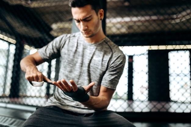 Donkerharige man gekleed in het grijze t-shirt wikkelt een handverband om zijn hand in de boksschool.
