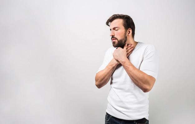 Donkerharige man houdt zijn handen op de keel. het lijkt erop dat hij verkouden is en binnenkort erg ziek zal worden. hij lijdt aan gedachtepijn. geïsoleerd op witte muur.