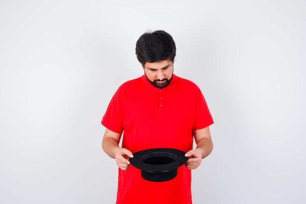 Donkerharige man kijkt in zijn hoed in rood t-shirt vooraanzicht.