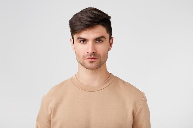 Donkerharige man, nonchalant gekleed, geïsoleerd over witte muur