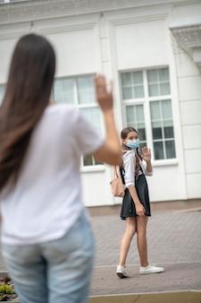 Donkerharige meisje in beschermend masker in goed humeur in de buurt van school en haar moeder neemt afscheid