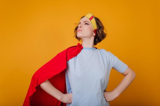 Donkerharige meisje in blauw t-shirt staande in zelfverzekerde pose en wegkijken