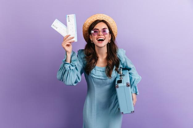 Donkerharige meisje met bril en strooien hoed houdt kaartjes en blauwe koffer. portret van reiziger in schattige retro jurk op lila muur.