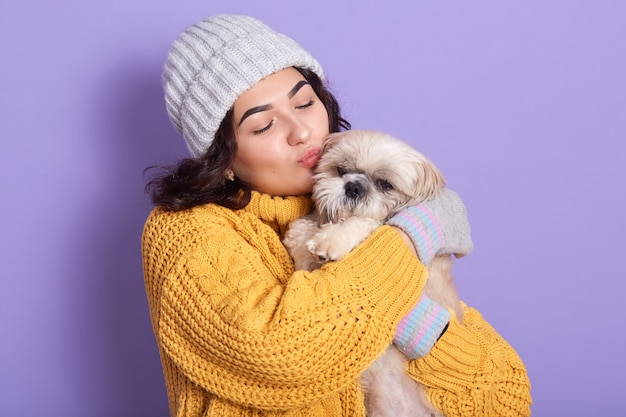 Donkerharige meisje met warme gele trui en pet die haar hondje kust, blithesome europese vrouw die haar liefde voor haar favoriete huisdier uitdrukt, dame houdt de ogen gesloten en poseert tegen de lila studiomuur.