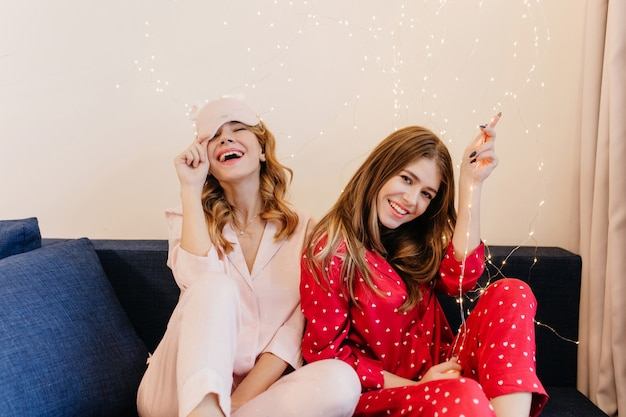 Donkerharige meisje poseren op de bank met geïnteresseerde gezichtsuitdrukking. gelukkige krullende dame in roze pyjama's en slaapmasker die op blauwe laag glimlachen.
