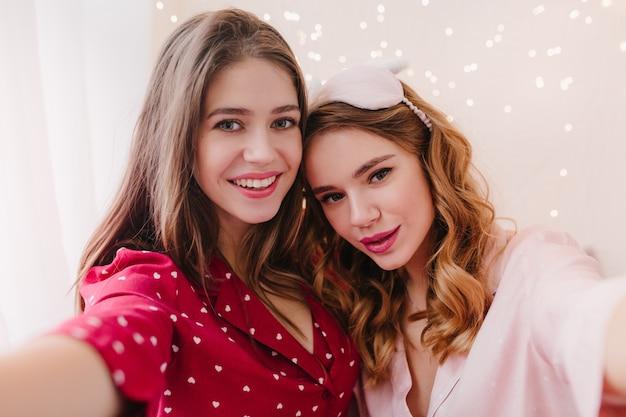 Donkerharige meisje positieve emoties uitdrukken en selfie maken in de ochtend. vrij gekrulde vrouw in roze eyemask tijd doorbrengen met zus.