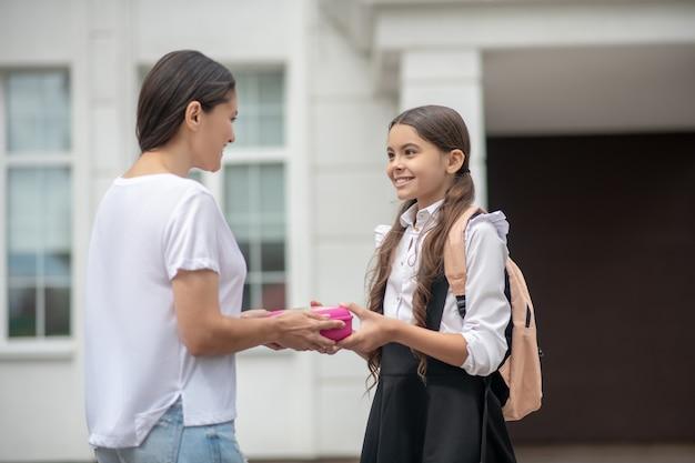 Donkerharige moeder die lunchbox met snack geeft aan gelukkig schoolmeisje dochter die zich dichtbij schoolingang bevindt
