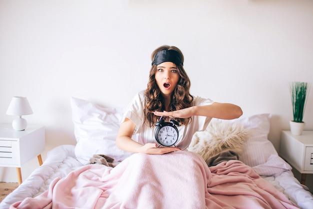 Donkerharige mooie jonge brunette wordt wakker in haar bed. de verwarde klok van de vrouwengreep in handen. later wakker geworden. verbaasd model kijk op camera met verwondering. slaapkamer.