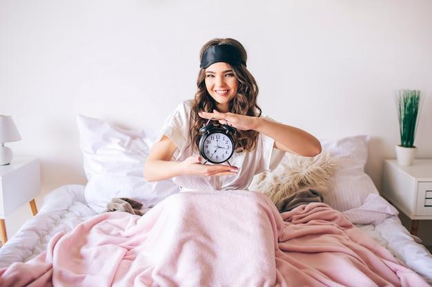 Donkerharige mooie jonge brunette wordt wakker in haar bed. de vrolijke aardige klok van de vrouwenholding in handen en glimlach. kijk recht op camera. slaapmasker op het voorhoofd. positief gelukkig model in slaapkamer.