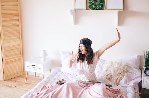 Donkerharige mooie jonge brunette wordt wakker in haar bed. stretching ahnd en geeuw. alleen in de slaapkamer. slaapmasker op het voorhoofd. wakker worden in de ochtend.