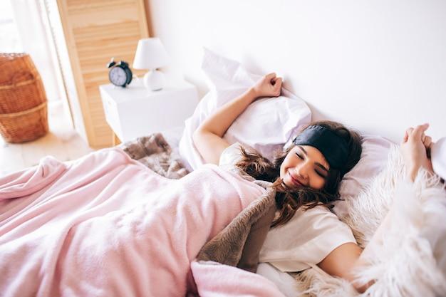 Donkerharige mooie jonge brunette wordt wakker in haar bed. uitrekkende handen en bosdy. liggend op bed in de slaapkamer. alleen. 's ochtends genieten van de tijd.