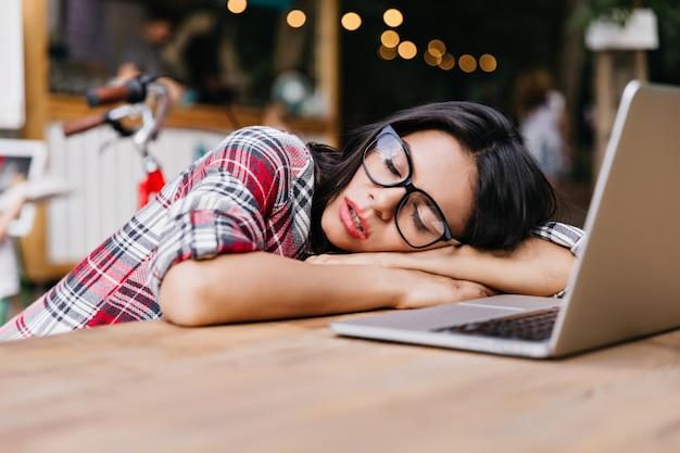 Donkerharige mooie student slapen in de buurt van computer. outdoor portret van charmante vrouwelijke freelancer in geruit overhemd restng na het werk.