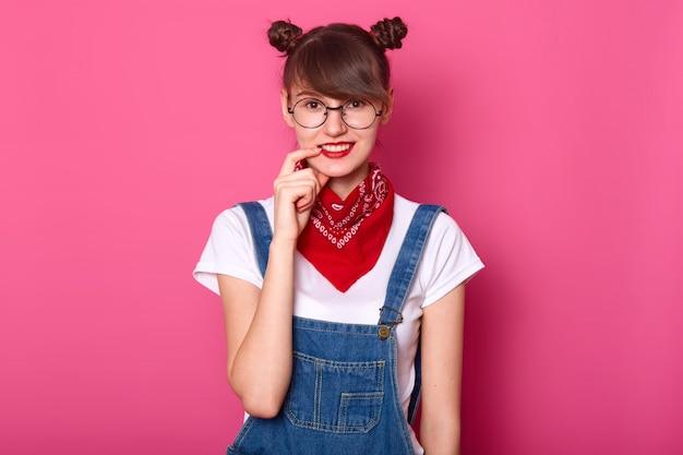 Donkerharige student glimlacht, houdt haar vinger op haar lip, ziet er verlegen uit. jong meisje draagt een t-shirt, denim overall met rode bandana op de nek.