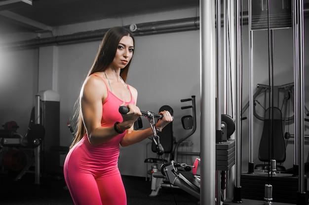 Donkerharige vrouw atleet in een trainingspak schudt handen biseps op de simulator in de sportschool.