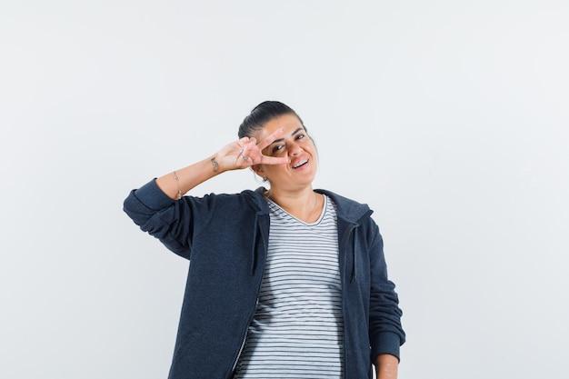 Donkerharige vrouw die v-teken over oog in overhemd toont