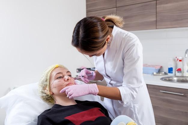 Donkerharige vrouw, een aziatische schoonheidsspecialiste, duwt een spuit om botox in de jukbeenderen van een jonge vrouw te injecteren om het formulier in het medische kantoor te corrigeren