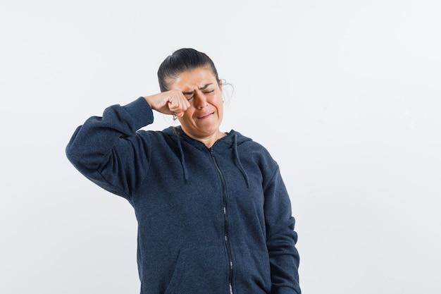 Donkerharige vrouw haar oog wrijven terwijl ze in jas huilen en er verdrietig uitziet. vooraanzicht.