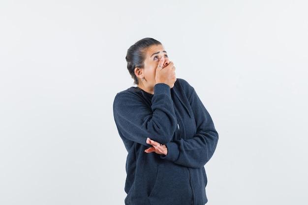 Donkerharige vrouw in jasje met hand op mond terwijl wegkijken en verbaasd kijken