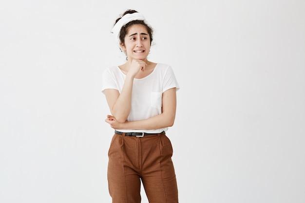 Donkerharige vrouw met een specifiek uiterlijk klemt haar tanden op elkaar en kijkt verward opzij, beseft dat haar fout, gekleed in een wit t-shirt en een bruine broek, tegen het kopieergebied poseert voor reclame