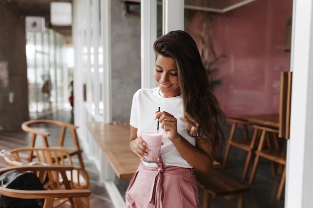 Donkerharige vrouw met glimlach die aardbeiyoghurt beweegt