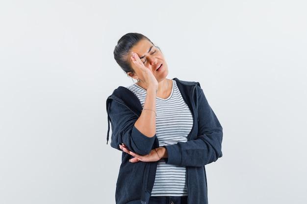 Donkerharige vrouw met hand op hoofd in shirt