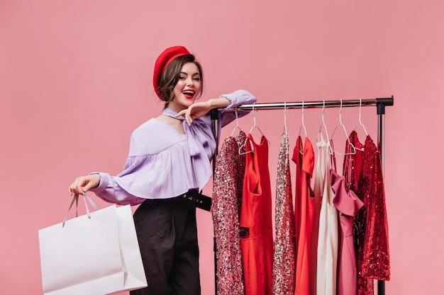 Donkerharige vrouw met rode lippenstift glimlacht, leunt op stand met kleding en houdt pakket op roze achtergrond.