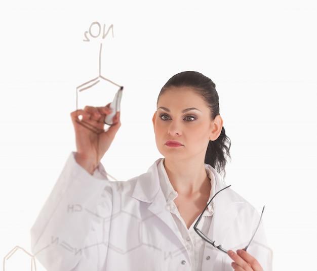 Donkerharige vrouw schrijft een formule op een wit bord
