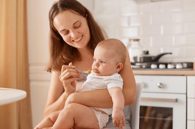 Donkerharige vrouw voedt haar dochtertje met fruit- of groentepuree, kijkt naar baby met charmante glimlach, houdt lepel in de hand, kijkt naar peutermeisje.