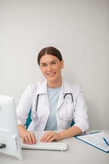 Donkerharige vrouwelijke arts in een wit gewaad zittend op het kantoor van de dokter