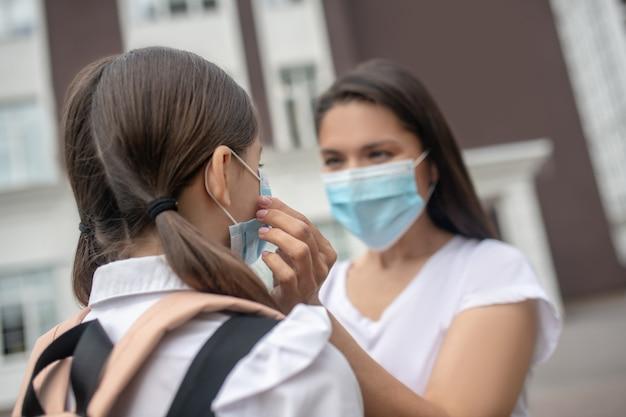 Donkerharige zorgzame moeder tot vaststelling van beschermend masker op haar dochterschoolmeisje op schoolplein