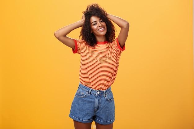 Donkerhuidig meisje met haar handen op krullend haar glimlachend vreugdevol staande tegen oranje muur