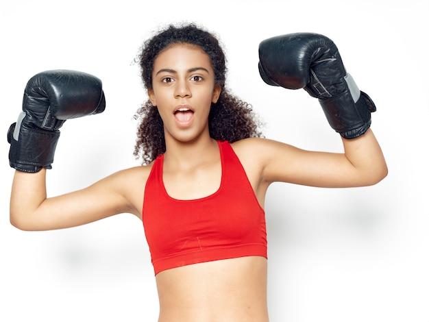 Donkerhuidige afro-amerikaanse vrouw poseren in een trainingspak en sporten in de studio