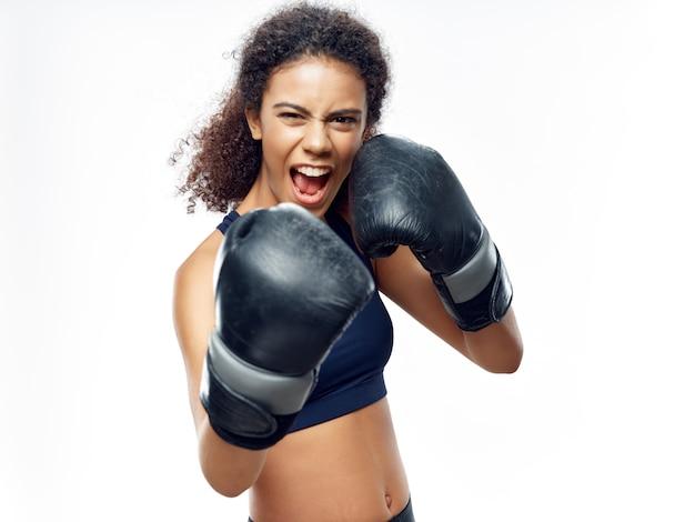 Donkerhuidige afro-amerikaanse vrouw poseren in een trainingspak en sportruimte te doen