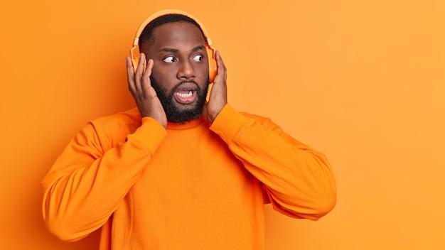 Donkerhuidige, bebaarde man staart afgeluisterde ogen houdt handen op stereo koptelefoon luistert muziek reageert op iets