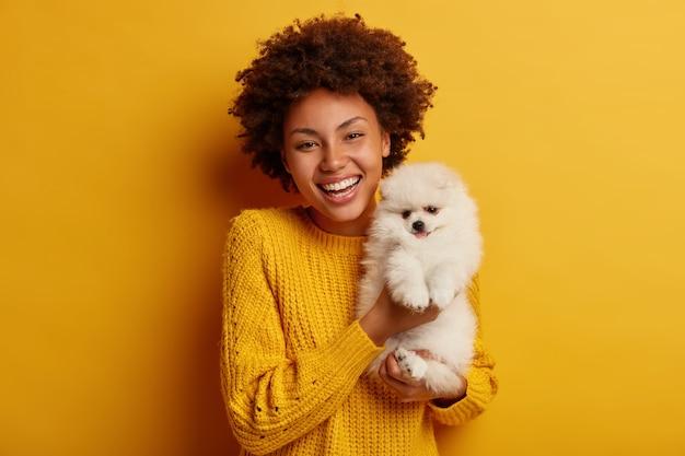 Donkerhuidige dame houdt lippen rond, wil schattig huisdier kussen, speelt met kleine puppy