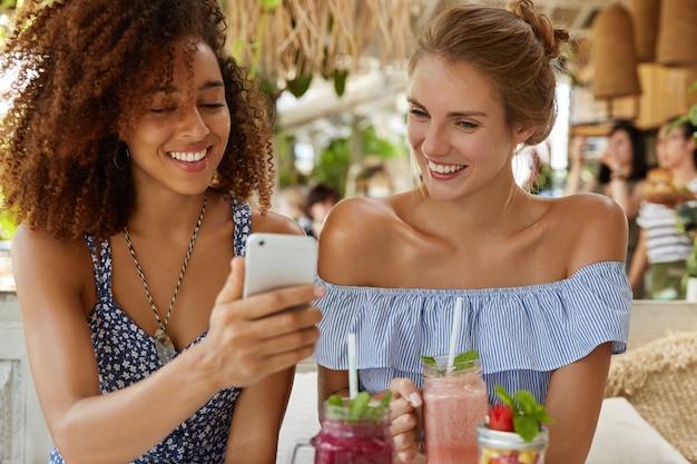 Donkerhuidige gekrulde vrouw met positieve uitdrukking toont foto's aan haar beste vriend op slimme telefoon, smoothie drinken. lesbisch koppel recreëren in restaurant met moderne gadget. vriendschap concept.